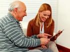 Familie mit einem Senioren schaut zusammen auf Tablet PC zu Hause